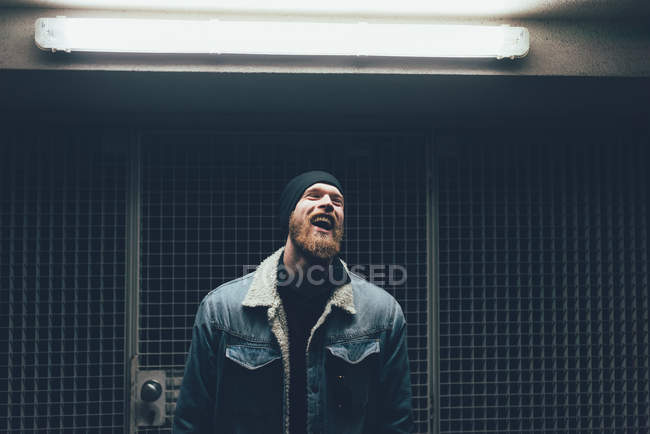 Hipster laughing in dark city doorway — Stock Photo