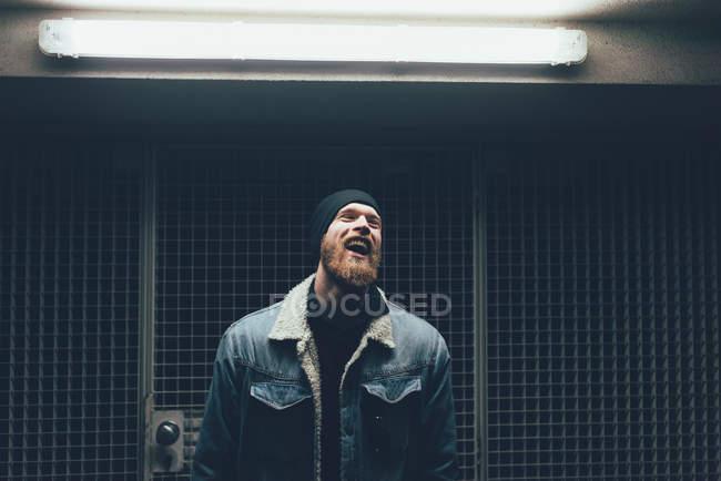 Hipster rindo na porta da cidade escura — Fotografia de Stock