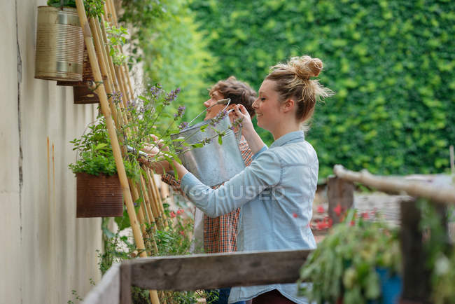 Young man and woman tending to plants — Stock Photo