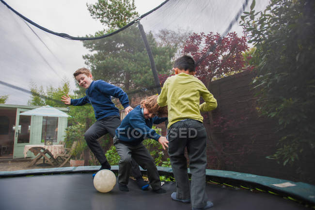 Boys on trampoline playing football — Stock Photo