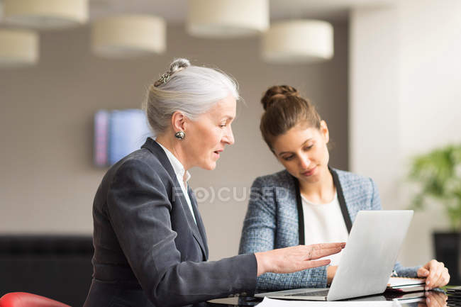 Businesswoman explaining to female colleague — Stock Photo