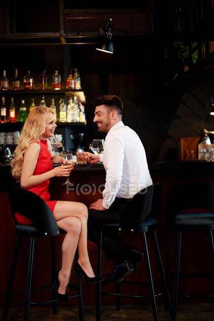 Пара сміючись сидячи в барі — стокове фото
