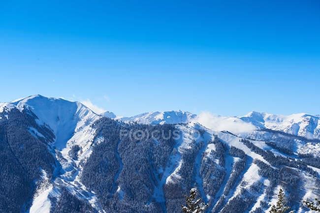 Couvert de neige, montagne et ciel bleu — Photo de stock