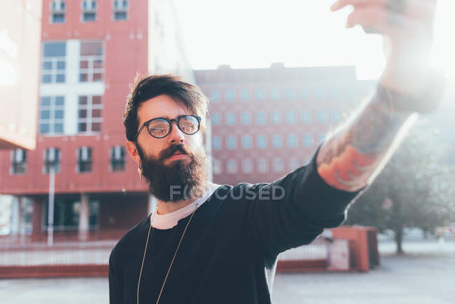 Male hipster taking smartphone selfie — Stock Photo