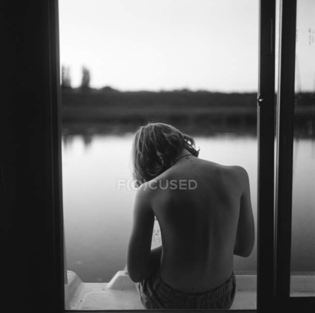 Garçon assis sur le bord de la péniche — Photo de stock