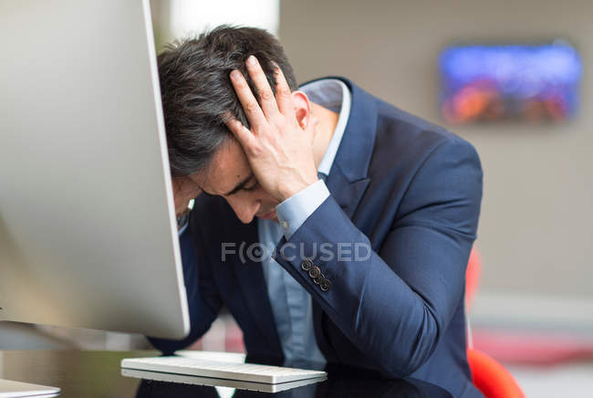 Stressed businessman at office computer — Stock Photo