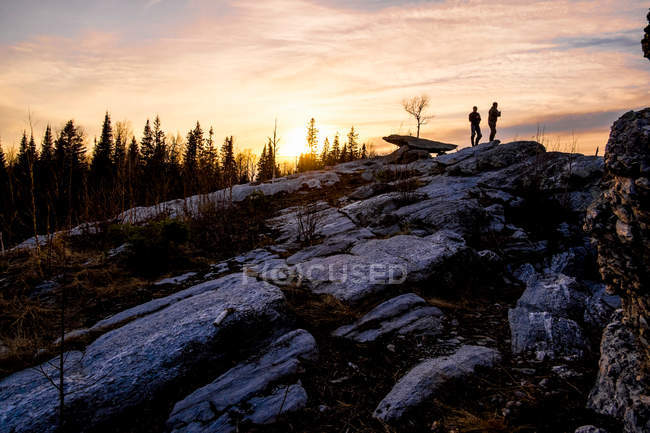 Silhouette des amis sur le dessus de roches — Photo de stock