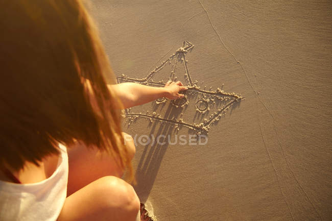 Young woman drawing in sand — Stock Photo