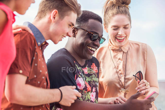 Young adult friends looking at smartphone — Stock Photo