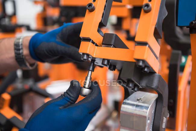 Hands adjusting screw — Stock Photo