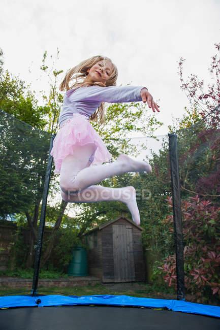 Girl bouncing on trampoline wearing tutu — Stock Photo