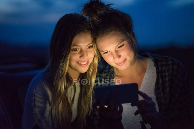 Friends using mobile phone — Stock Photo