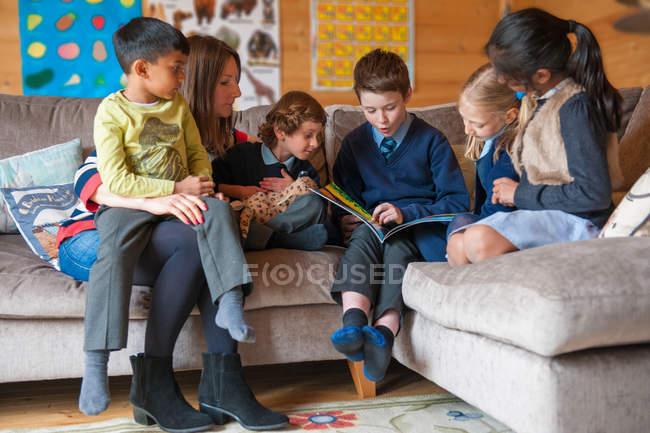 Boy bei Tagesmüttern Buch an Freunde — Stockfoto
