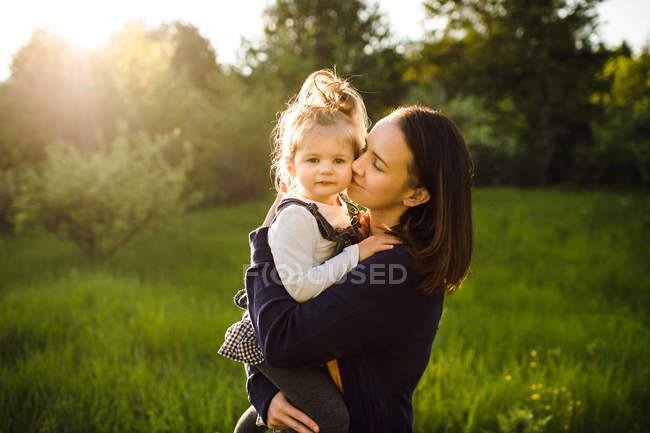 Mujer besando a su hija - foto de stock