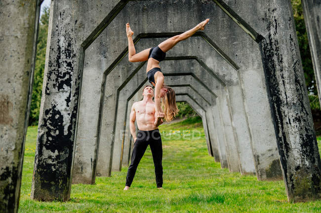 Practicing yoga below concrete bridge — Stock Photo