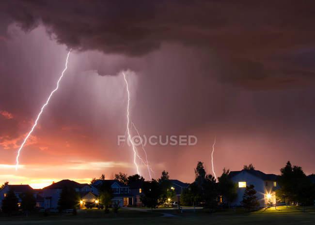 Blitz in orangefarbenem Himmel über Stadtgebiet — Stockfoto