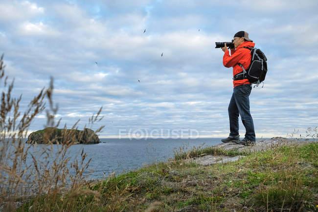 Мужчина фотографирует побережье — стоковое фото