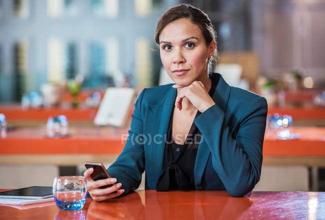 Businesswoman using mobile phone in cafe — Stock Photo