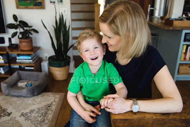 Мальчик сидит на коленях матери — стоковое фото