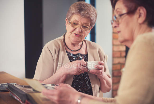 Women looking at old photographs — Stock Photo