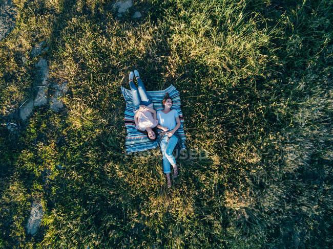 Amigos deitado em cobertor — Fotografia de Stock