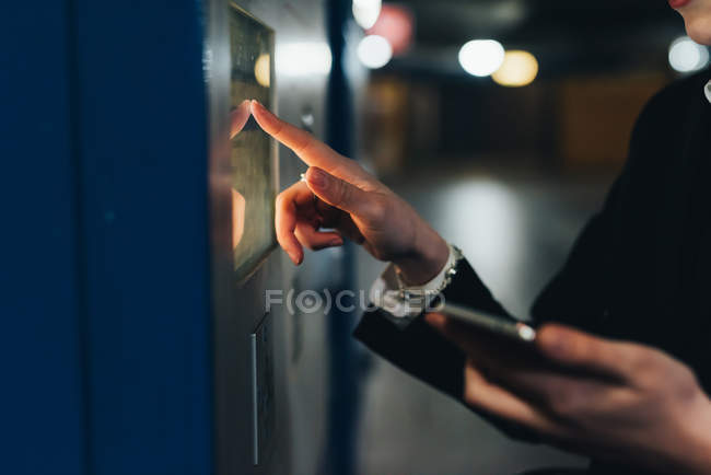 Businesswoman using ticket machine — Stock Photo