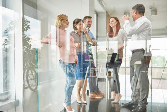 Kollegen, die im Büro stehen und reden — Stockfoto
