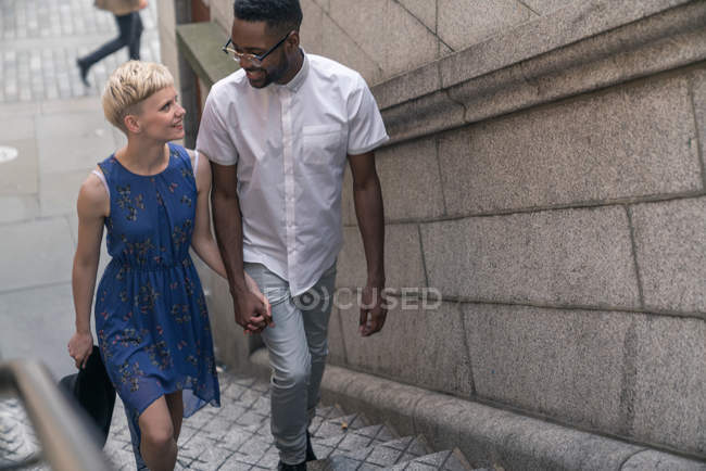 Young couple walking up steps — Stock Photo