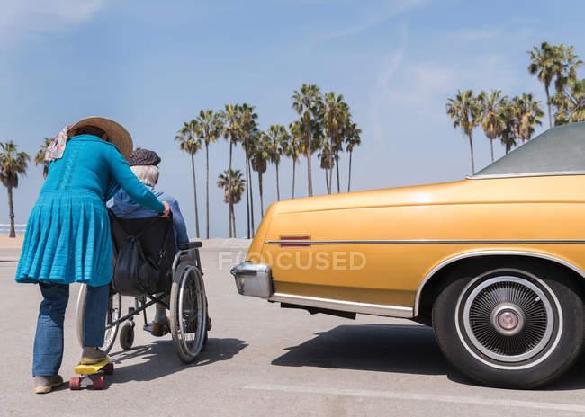 Woman pushing husband in wheelchair — Stock Photo