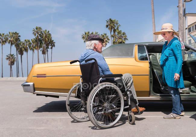 Donna anziana che chatta con il marito in sedia a rotelle — Foto stock