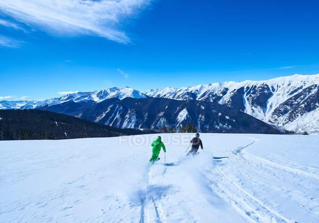 Двое мужчин лыжах вниз по склону — стоковое фото