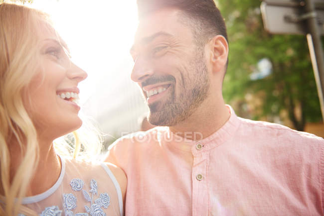 Couple in sunlight face to face smiling — Stock Photo