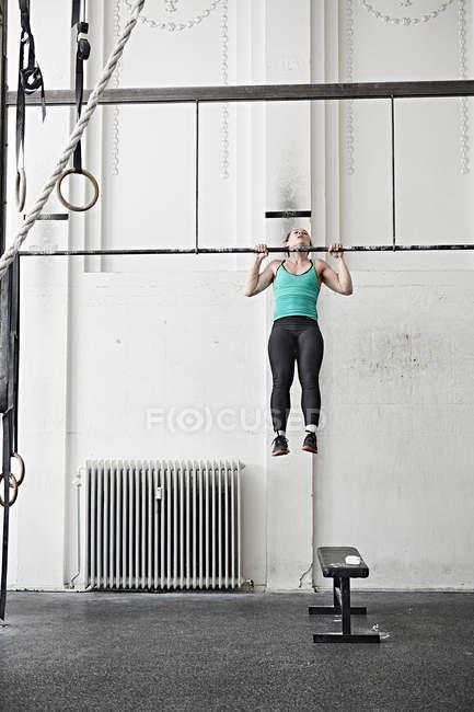 Woman doing chin-up — Stock Photo