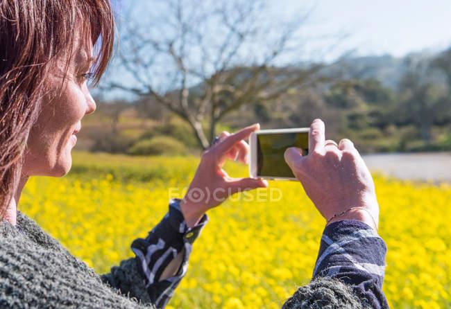 Зрелая женщина принимать изображение с помощью смартфона — стоковое фото