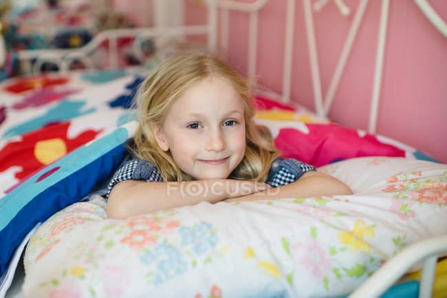Retrato da menina deitada na cama — Fotografia de Stock
