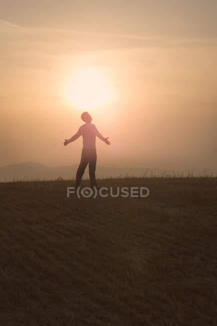 Homem em pé no campo ao pôr do sol — Fotografia de Stock