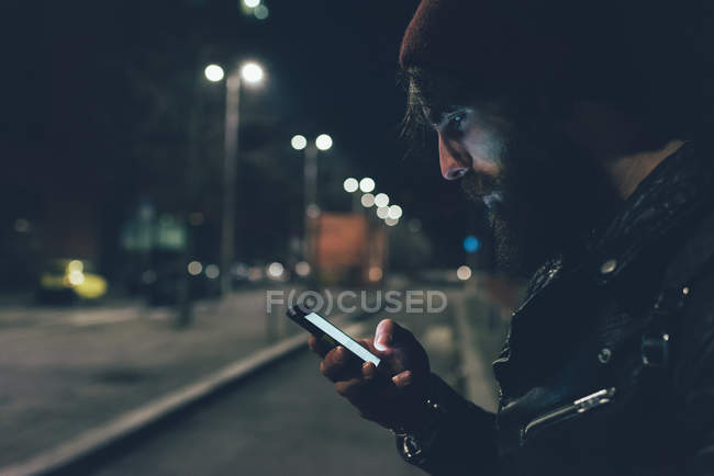 Hipster on city street looking at smartphone — Stock Photo
