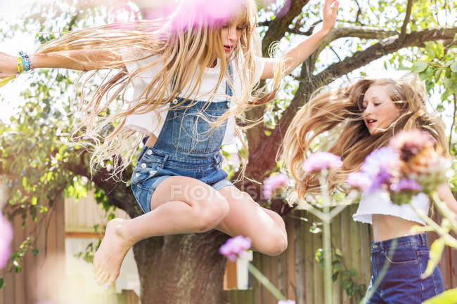 Girls in garden jumping in air — Stock Photo