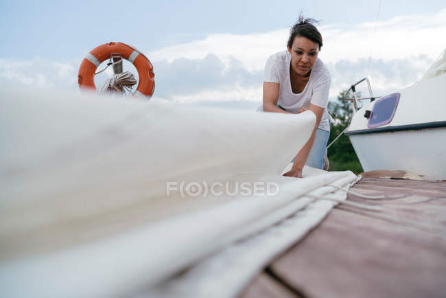 Young woman folding boats sail — Stock Photo