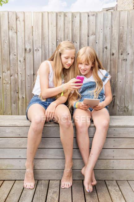 Девушки сидят вместе — стоковое фото