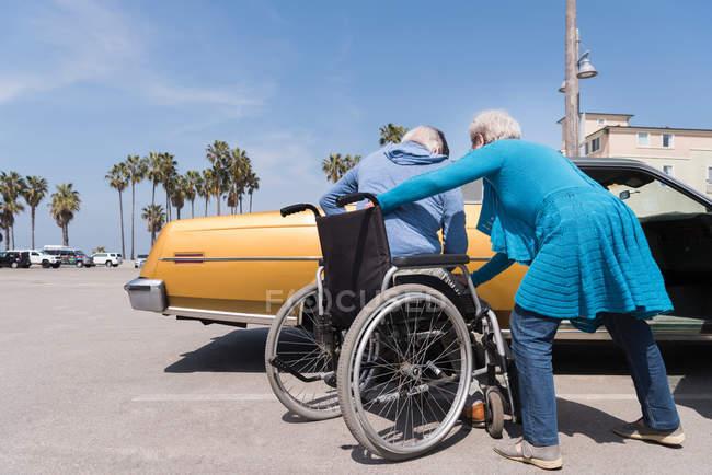 Femme aidant mari en fauteuil roulant — Photo de stock