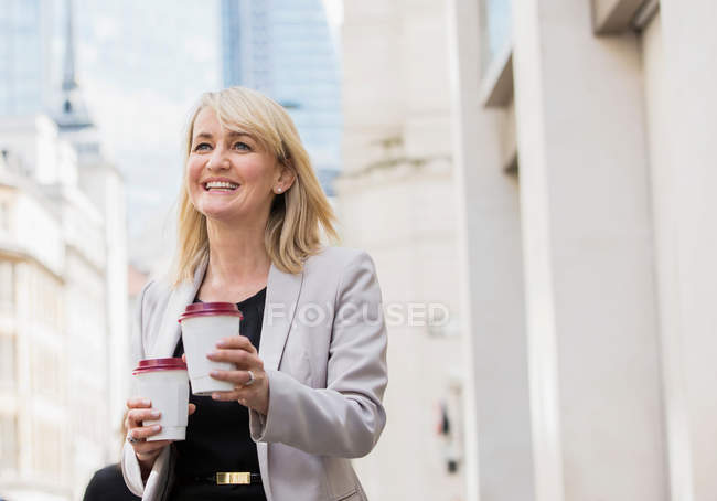 Businesswoman with coffee cups — Stock Photo