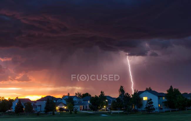 Forked Lightning in orangefarbenen Himmel über Stadtgebiet — Stockfoto