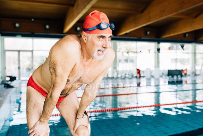 Se penchant sur la capture de l'homme respire par piscine — Photo de stock