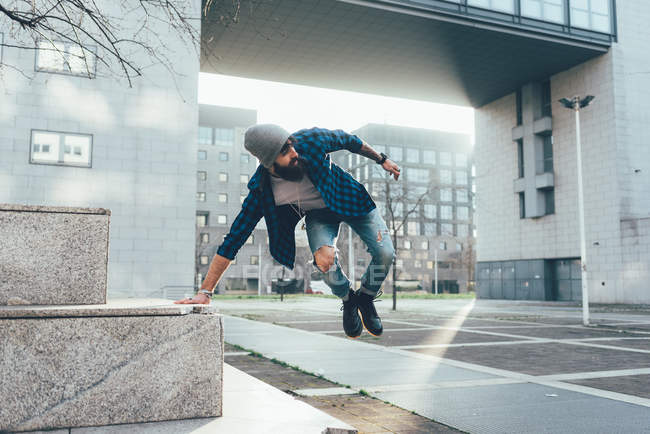 Hipster jumping mid air practicing parkour — Stock Photo