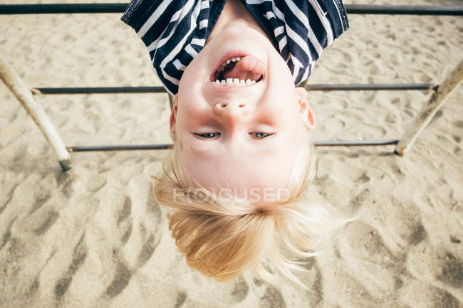 Boy hanging upside down — Stock Photo