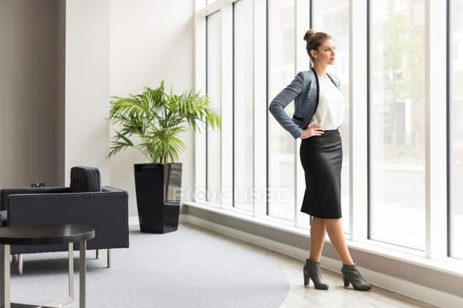 Businesswoman looking through office window — Stock Photo