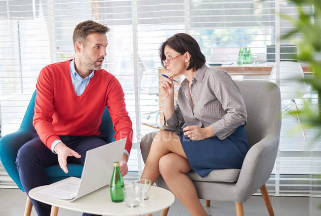 Colleagues using laptop having discussion — Stock Photo