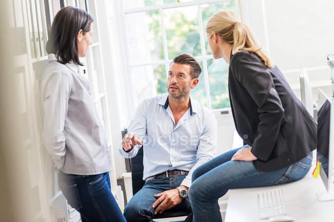 Designer explaining idea to female colleagues — Stock Photo