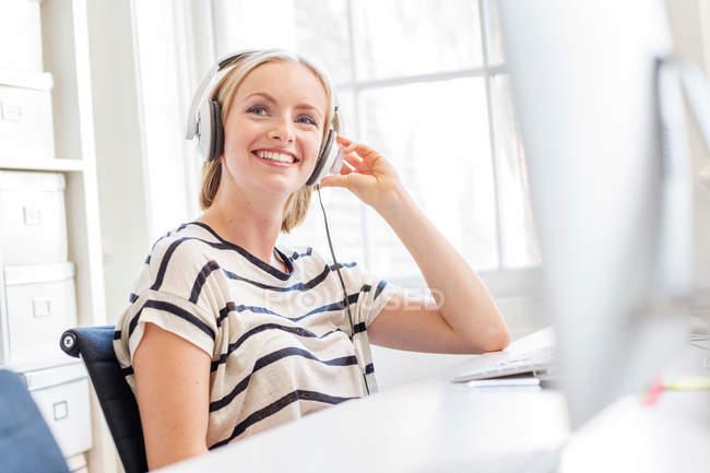 Designer féminin écoutant des écouteurs — Photo de stock